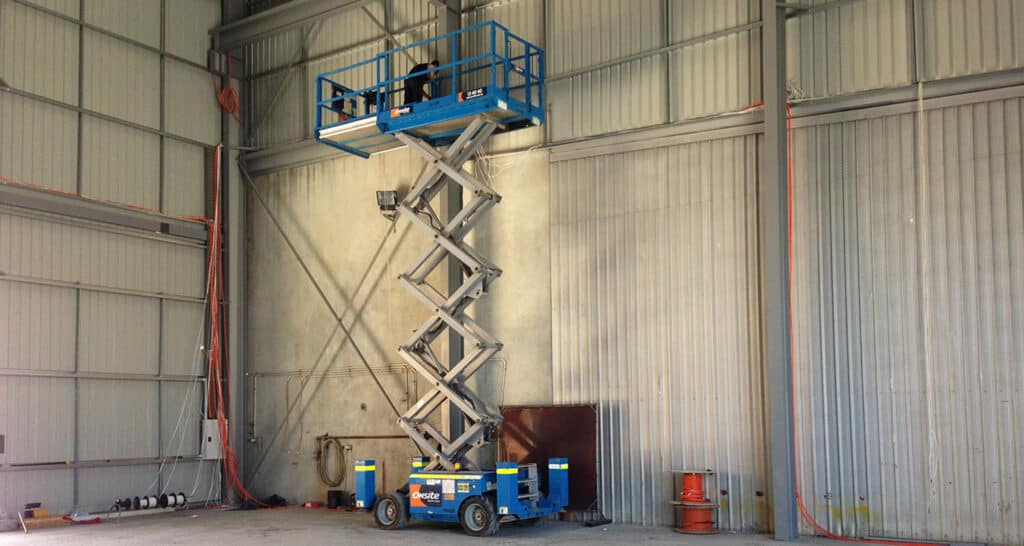 New construction electrician performing electrical services in a scissor lift